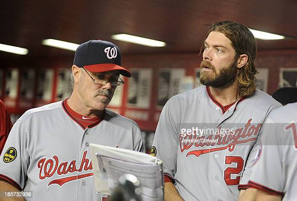 Batting coach Rick Schu and outfielder Jayson Werth of the Washington Nationals talk in the dugout in the game against the Arizona Diamondbacks at...