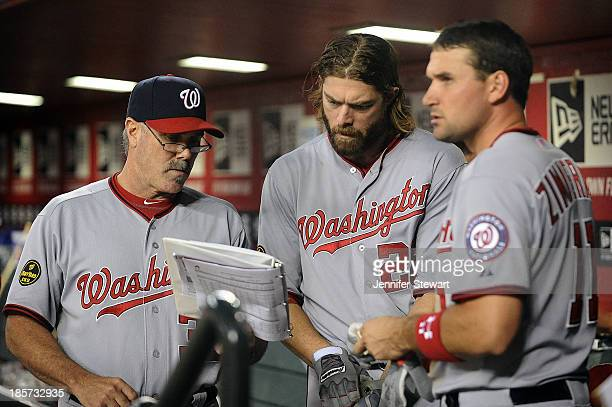 Batting coach Rick Schu outfielder Jayson Werth and infielder Ryan Zimmerman of the Washington Nationals talk in the dugout in the game against the...