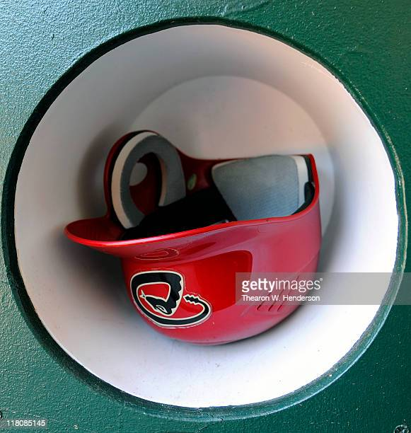 A batting helmet of an Arizona Diamondback sits in the rack at the end of the dugout before the start of a MLB baseball game between the Diamondbacks...