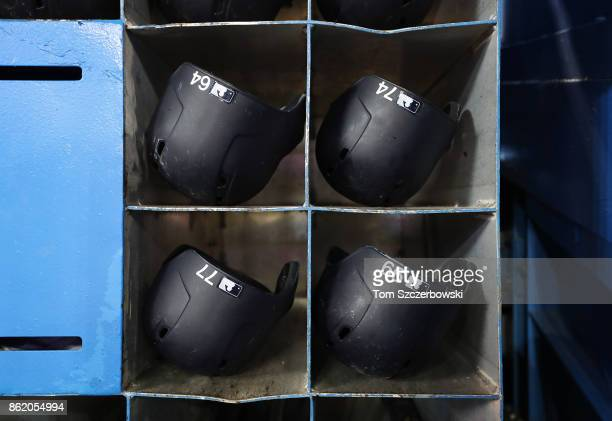 Batting helmets of Garrett Cooper of the New York Yankees and Ronald Torreyes and Aaron Judge and Clint Frazier sit in the helmet rack in the dugout...