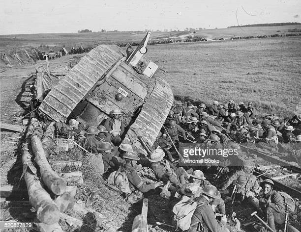 Battle of Cambrai Men of the 20th Manchesters resting by a tank disabled of sideslipping down a railway embankment near Premont 8th October 1918 25th...
