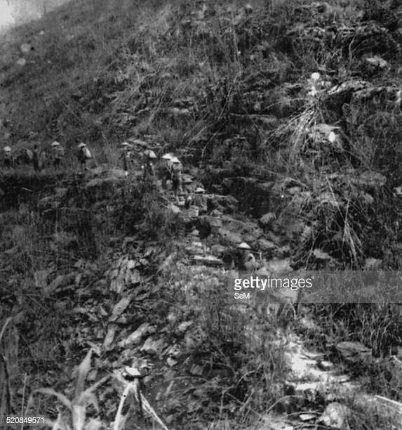 Battle of Diem Bien Phu 1954-Vietminh Dien Bien Phu conscripted labourers carring on shoulder and climbing up to slop.