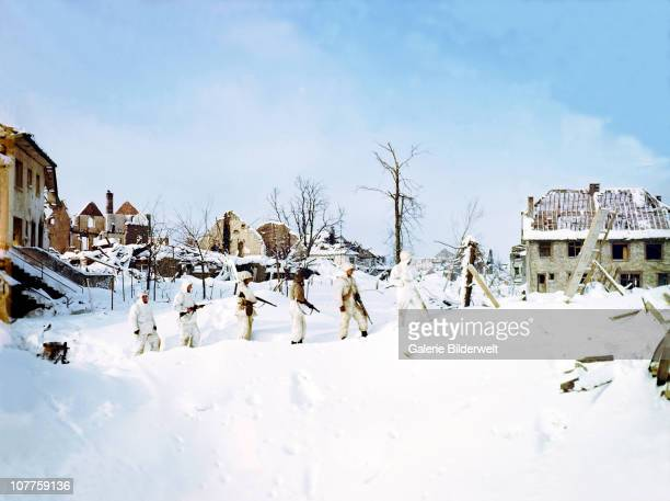 Battle of the Bulge Six United States soldiers from the 7th Armored Division are patrolling St Vith during the Battle of the Bulge also known as the...