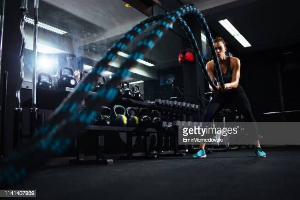 battle ropes session at the gym - battle stock pictures, royalty-free photos & images