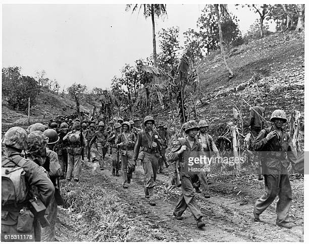 Battle weary Marines, right, leave the front lines of Saipan as fresh Leatherneck reserves, left, come up to replace them.