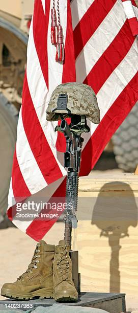 a battlefield memorial cross rifle display stands at attention, during a memorial service. - boots rifle helmet stock pictures, royalty-free photos & images