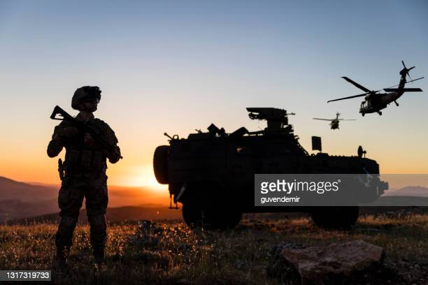 battlefield with a soldier, armored vehicle and flying helicopters at sunset - helicopter stock pictures, royalty-free photos & images