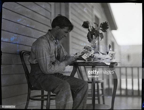 Battling Nelson lightweight boxer is shown seated at a table reading cards that wish him well