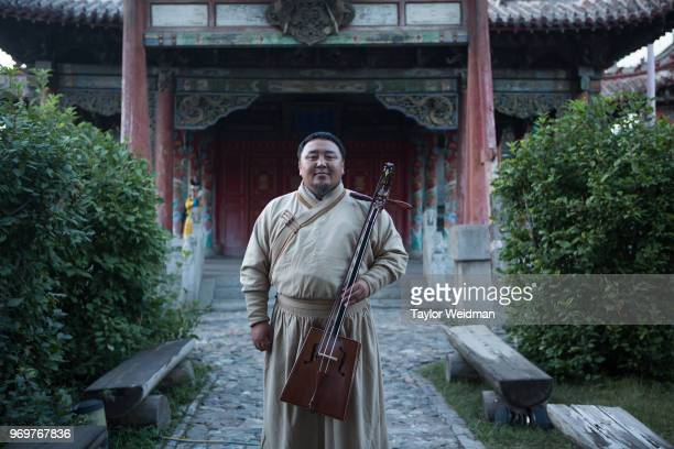 Batzorig stands for a portrait at a performance at Choijin Lama Temple in Ulaanbaatar Mongolia The Morin Khuur or horsehead fiddle is a traditional...