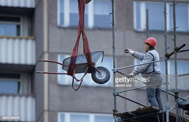 Bauarbeiter einer Abrissfirma mit Schubkarre auf dem Lenindenkmal am Leninplatz