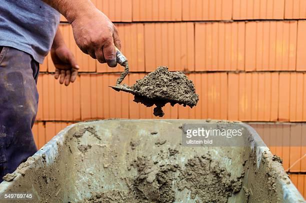 Bauarbeiter mit Maurerkelle beim Mauern eines Rohbaus in Massivbauweise Symbolfoto der Schwarzarbeit und Nachbarschaftshilfe