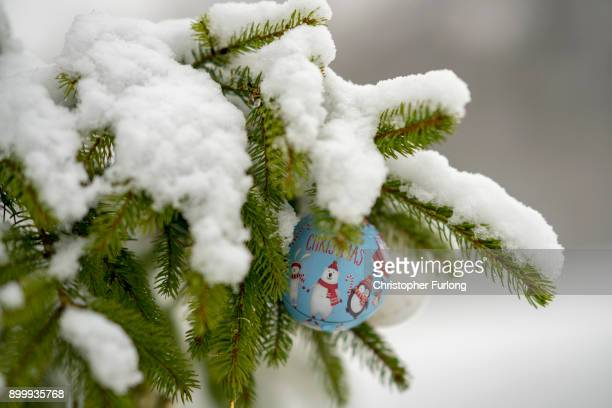 Bauble hangs from a snow covered Christmas tree in in Shibden Hall Park on December 29, 2017 in Halifax, England. Travelers are being warned of...