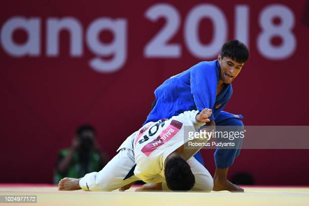 Baul An of Korea fights against Shakhram Ahadov of Uzbekistan during Men's Judo 66kg Semifinals at Plenary Hall on day eleven of the Asian Games on...