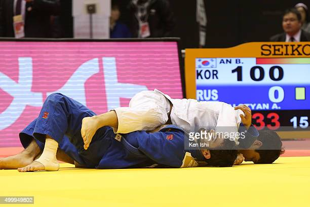 Baul An of Korea holds Arsen Galstyan of Russia for ippon in the Men's 66kg preliminary at Tokyo Metropolitan Gymnasium on December 4 2015 in Tokyo...