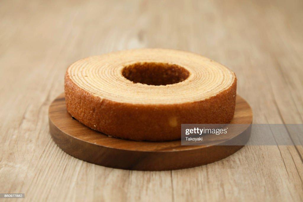 baumkuchen German doughnut cake on wood plate on table : Stock Photo