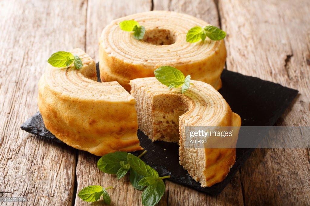 Baumkuchen, translated as tree cake, is a many-layered sponge cake baked on a rotating cylinder close-up. horizontal : Stock Photo