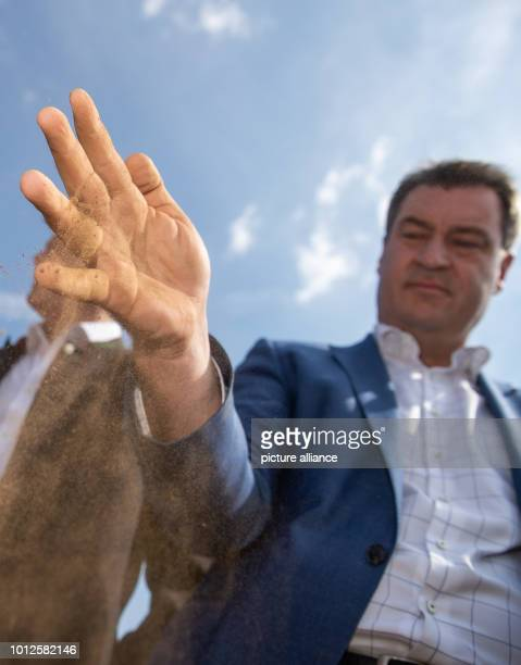 Markus Söder Minister President of Bavaria lets dried soil of a field trickle out of his hand during his visit to a farm Together with the Bavarian...