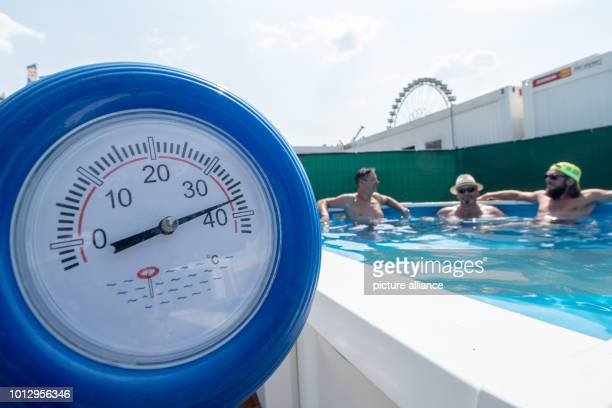 Bavaria, Straubing: A thermometer shows a temperature of 38 degrees, while the fitters of an exhibition stand for pools cool down during a break on...