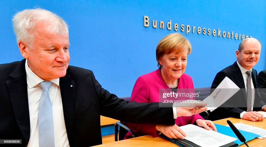 Bavarian Christian Social Union (CSU) leader and designated Interior minister Horst Seehofer (L) hand s his name plate to Social Democrats party (SPD) leader and designated German Finance Minister and Vice-Chancellor Olaf Scholz (R) past German Chancellor Angela Merkel as they get ready to address a press conference at the Federal Press Conference in Berlin, on March 12, 2018 prior to the signature of the chancellor's conservative CDU/CSU and the SPD's coalition contract for a new government. / AFP PHOTO / John MACDOUGALL