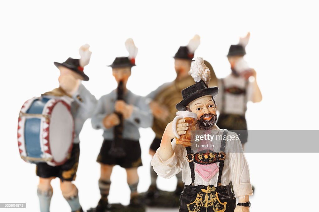 Bavarian figurine drinking beer with figurines playing music in background : Stock Photo