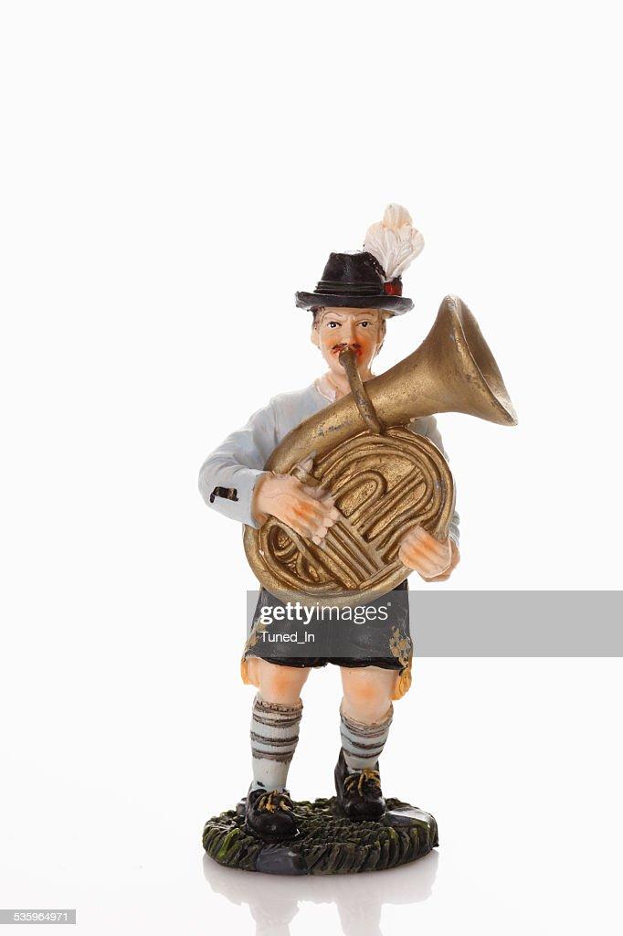 Bavarian figurine playing tuba on white background : Stock Photo