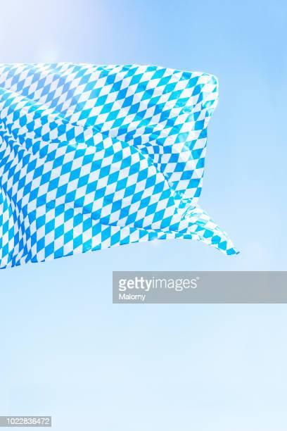 bavarian flag against clear blue sky during sunny day. germany, bavaria, munich, oktoberfest - bayern stock-fotos und bilder