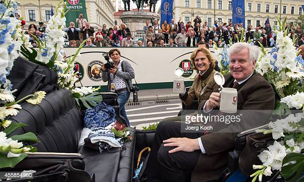 Bavarian Governor Horst Seehofer and his wife Karin Seehofer cheer with beer mugs during the traditional costume parade on day two of the 2014...