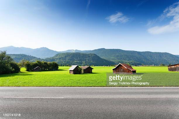 bavarian landscape with huts along the road, side view - village stock pictures, royalty-free photos & images