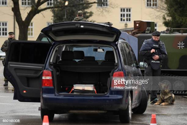 Bavarian police officer and his explosives detection dog search a vehicle at a checkpoint during a demonstration as part of the GETEX antiterror...