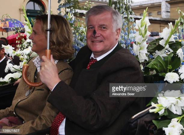 Bavarian state premier Horst Seehofer and his wife Karin smile after they got their noses blackened by a harlekin during their carriage ride at the...