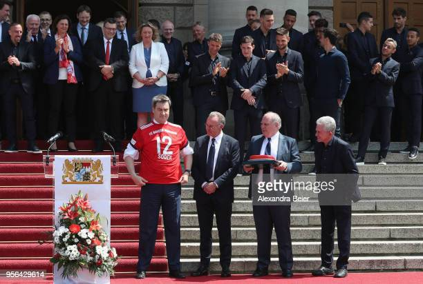 Bavarian state premier Markus Soeder poses with a FC Bayern Muenchen jersey next to CEO of FC Bayern KarlHeinz Rummenigge president Uli Hoeness and...