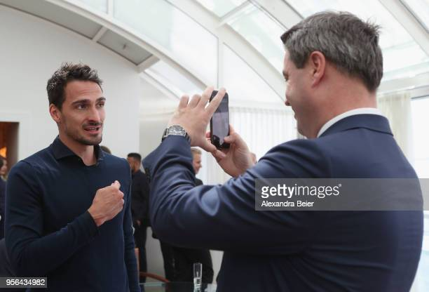 Bavarian state premier Markus Soeder takes a picture of Mats Hummels of FC Bayern Muenchen during a reception honoring the team's German Championship...
