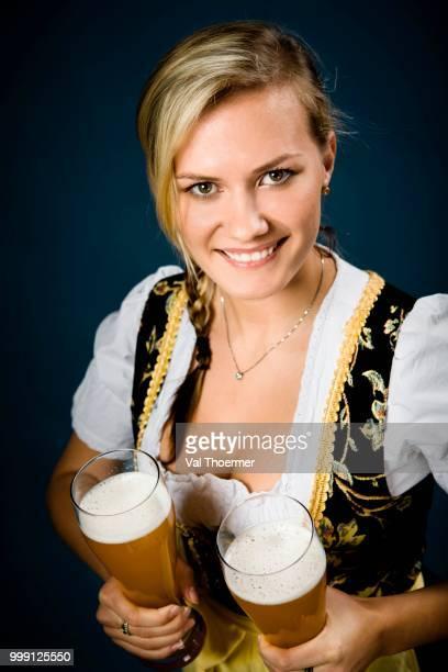 bavarian woman dressed in traditional dirndl, holding beer glasses - val thoermer stock-fotos und bilder