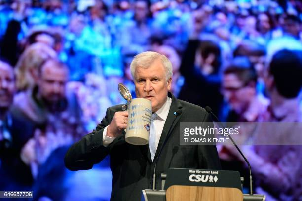 Bavaria's State Premier and leader of the conservative Christian Social Union Horst Seehofer takes a sip from his beer mug as he gives a speech...