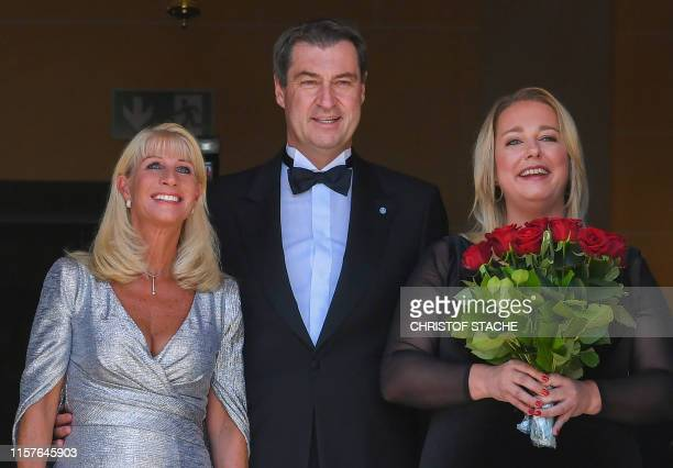 Bavaria's State Premier Markus Soeder his wife Karin Soeder and Katharina Wagner greatgranddaughter of German composer Richard Wagner pose as they...