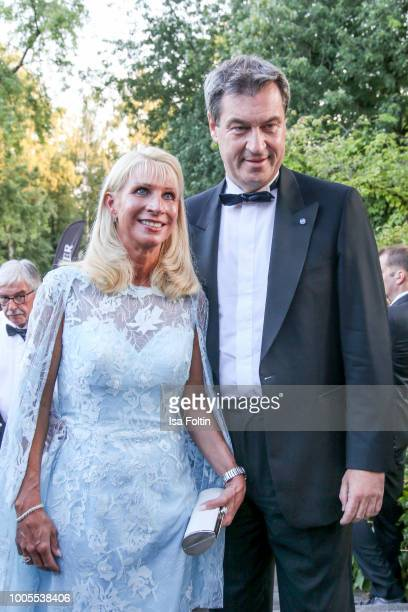 Bavaria's State Premier Markus Soeder poses next to his wife Karin Baumueller during the opening ceremony of the Bayreuth Festival at Bayreuth...