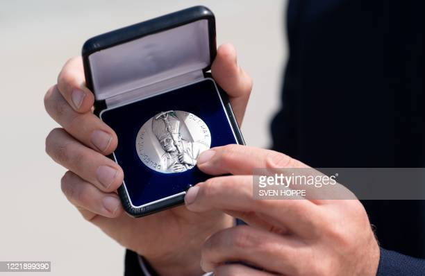 Bavaria's state premier Markus Soeder presents a medal he was given by former pope Benedict XVI during the former pope's departure from the airport...