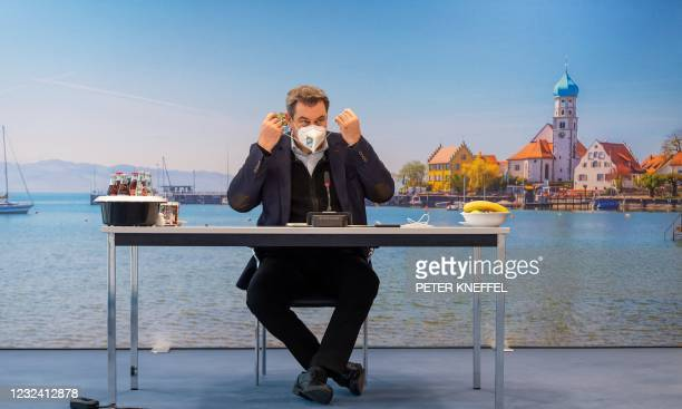 Bavaria's State Premier Markus Soeder takes off his face mask as he prepares to lead a video-conferenced cabinet meeting on April 20, 2021 in Munich,...