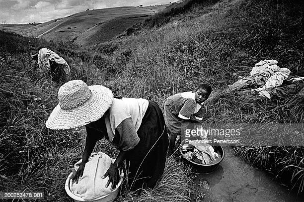 Bawinile Zulu age 11 helps her mother wash the family clothes in a river on August 20 2002 in Nqabeni a rural area in Port Shepstone South Africa...