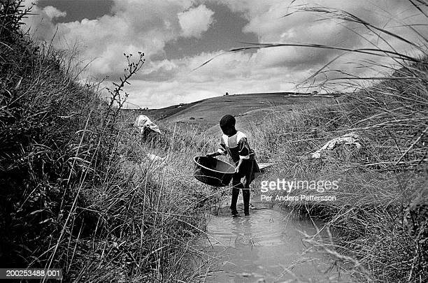 Bawinile Zulu age 11 washes the family clothes in a river on August 20 2002 in Nqabeni a rural area in Port Shepstone South Africa Bawinilie was...