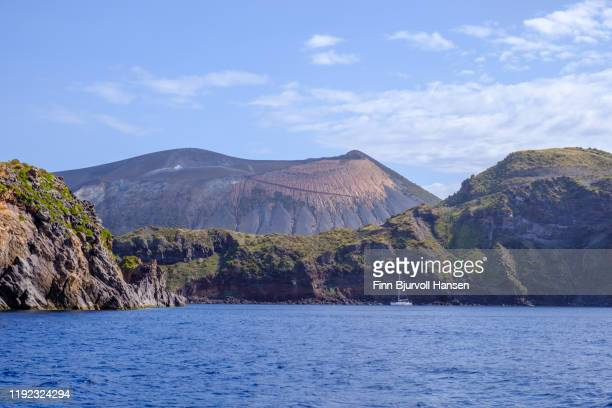 bay and sailing boat at the eolian and lipari island vulcano, the vulcano in the background - finn bjurvoll stockfoto's en -beelden