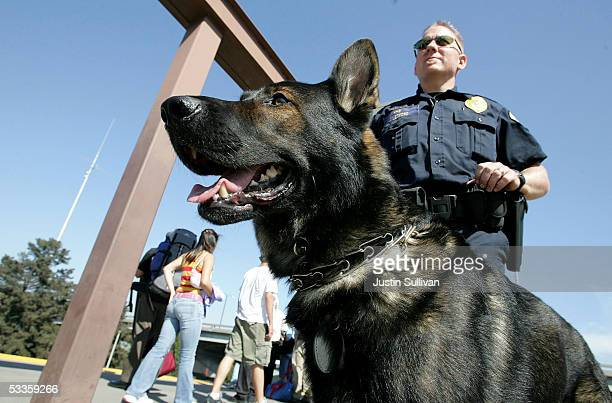 Bay Area Rapid Transit police officer Jason Ledford patrols with his bombsniffing dog Andy at the Oakland Coliseum station August 11 2005 in Oakland...
