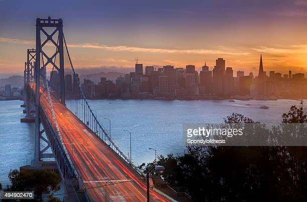 bay bridge and san francisco skyline at sunset - bay bridge stock pictures, royalty-free photos & images