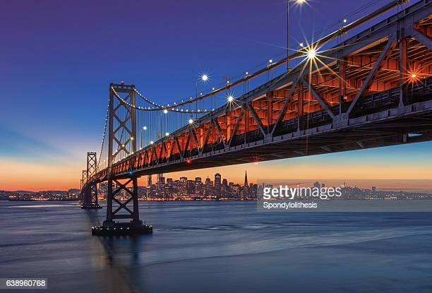 bay bridge and san francisco skyline at sunset - san francisco california stock photos and pictures