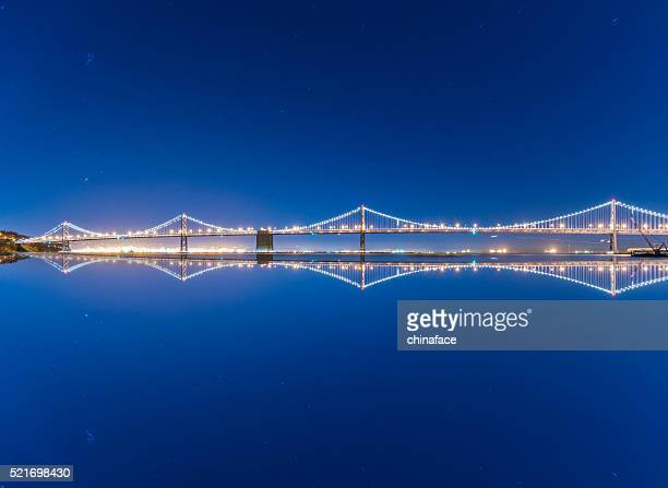bay bridge and skyline of san francisco at night - bay bridge stock pictures, royalty-free photos & images