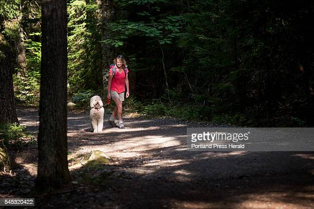 Bay Ellis of Mt Desert walks her dog Maggie Rose a golden doodle up Acadia Mountain on the quiet side of Acadia National Park off Route 102 Tuesday...
