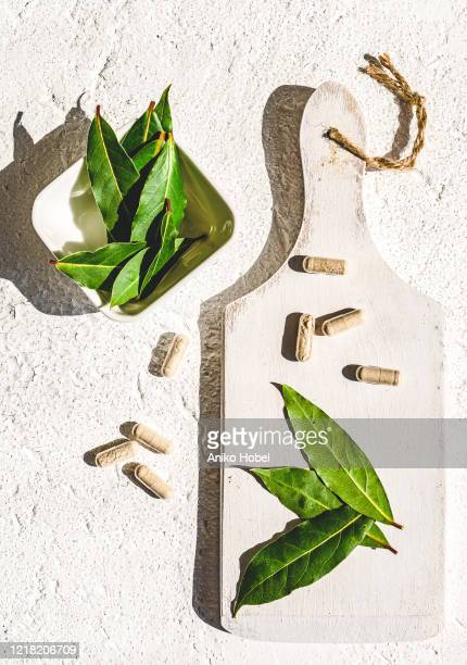 bay leaves and capsules - aniko hobel stock pictures, royalty-free photos & images