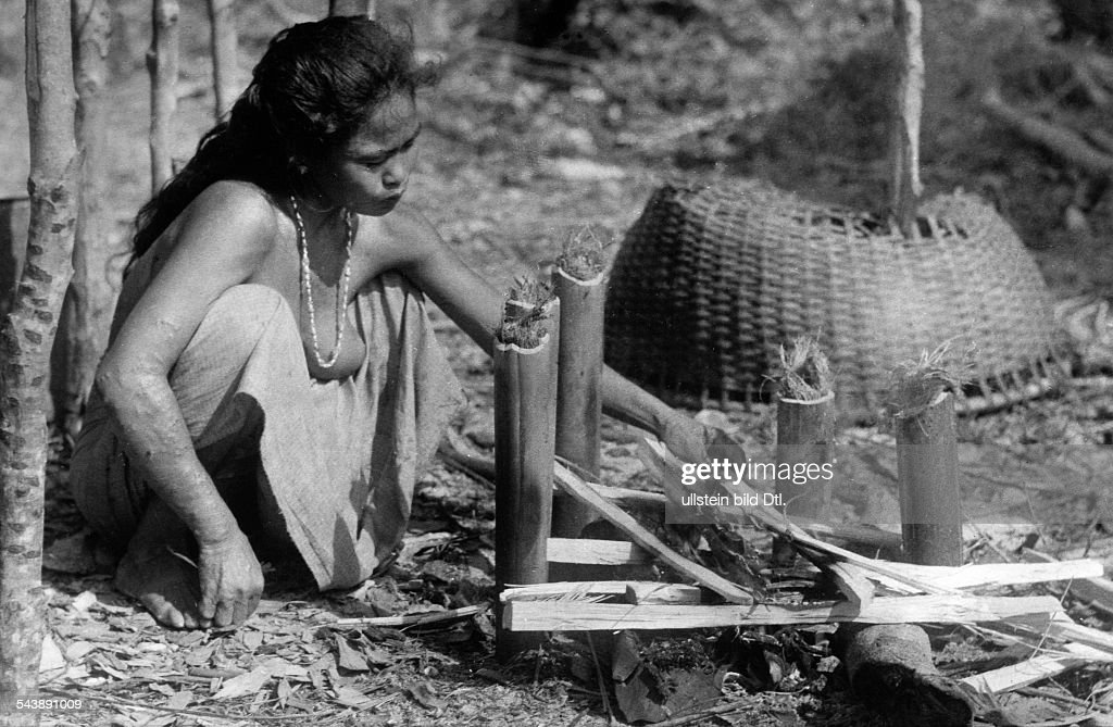 A Moken woman at a log fire, preparing the caught fishes (Series: 15 pictures) - ca. 1940- Photographer: Hugo Adolf BernatzikVintage property of ullstein bild