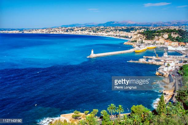 """bay of nice : entrance of the port and the """"promenade des anglais"""", between the beach and the city center - nice france stock pictures, royalty-free photos & images"""