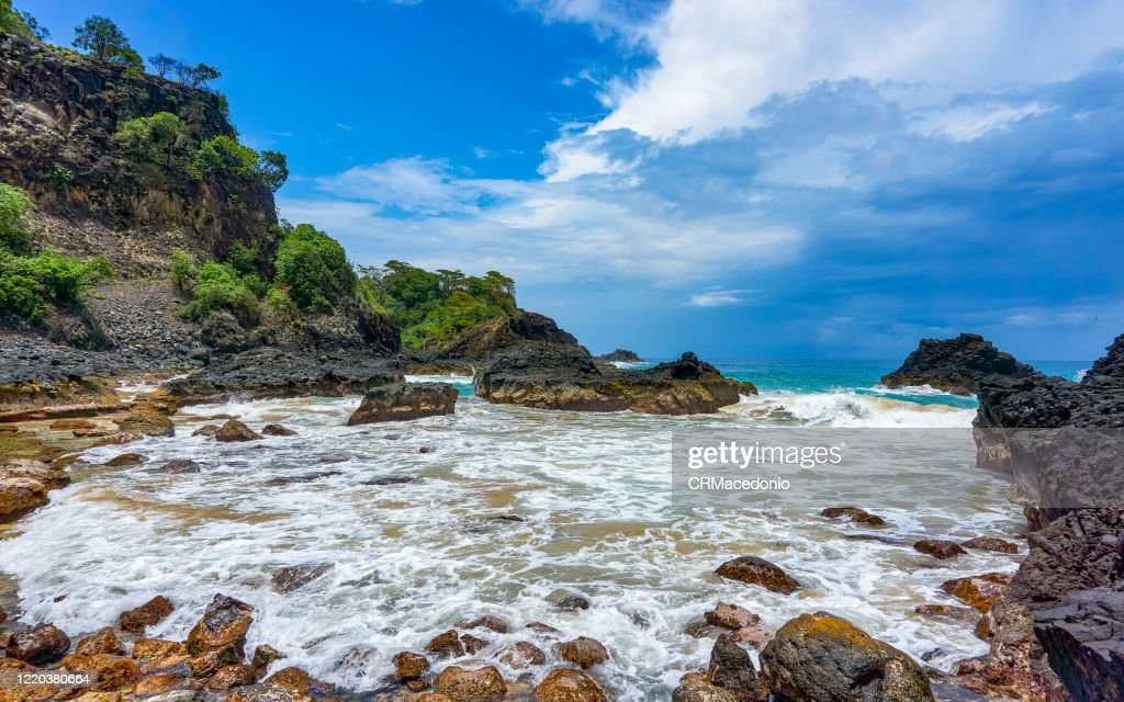 Bay of Pigs (Baia dos Porcos), in Fernando de Noronha. Volcanic stones, crystal clear sea with various shades of green in the background, and natural pools carved in the rocks. : Stock Photo